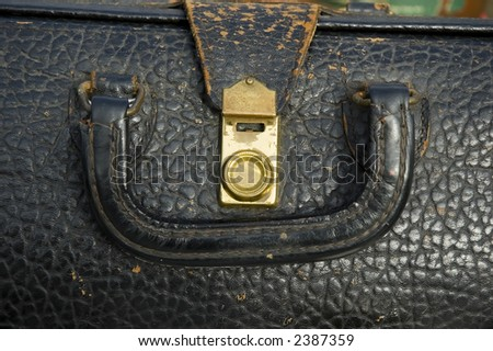 Vintage leather doctor bag showing the brass clasp and worn leather handle,used in making house calls
