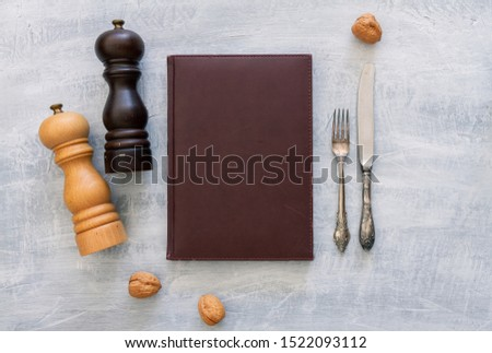 Vintage leather menu with rustic steel or metal silverware with copy space. Top view or above view composition #1522093112
