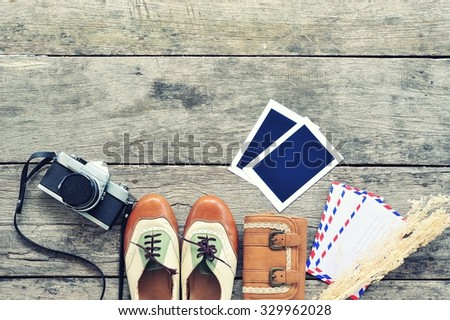 Vintage leather shoes ,leather wallet,letter,photo frame and camera on wood background.