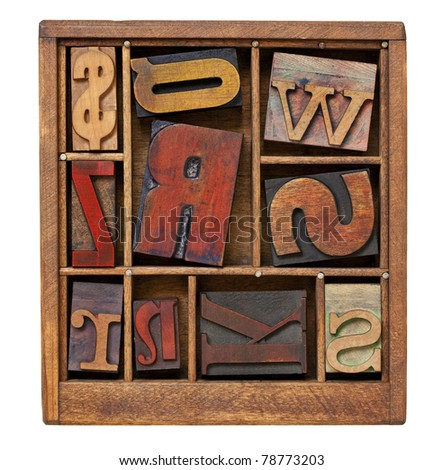 vintage letterpress printing blocks in small wooden typesetter box with dividers, isolated on white