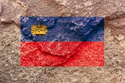 Vintage Liechtenstein national flag icon pattern isolated on weathered strong rock wall background, abstract positive Liechtenstein politics religion history culture concept texture wallpaper