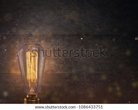 Vintage light bulb on dark background with empty space for text.