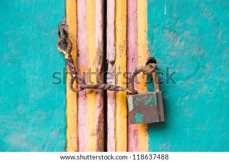 Vintage lock and chain on an old colorful wooden door