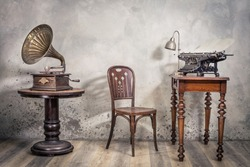 Vintage loft room with old typewriter and lamp on wooden desk, antique chair and classic gramophone with brass horn  front concrete wall background with shadows. Retro style filtered photo