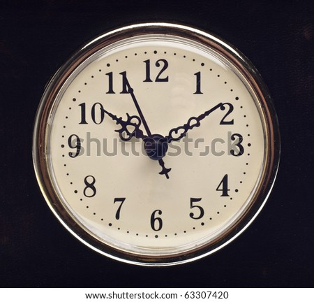 Vintage Look Clock on Black Leather Hands at 10 and 2.