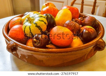 Vintage looking Many different fruits and vegetables in a bowl including oranges and chestnuts and pumpkins