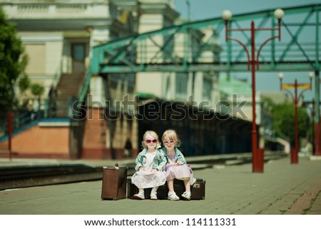 Vintage looking picture of small girls with luggage at the railway station