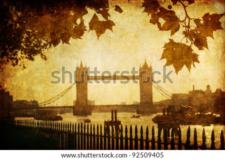vintage looking picture of the tower bridge framed from autumnal leave canopy