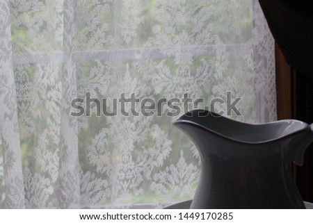 Vintage looking pitcher and white lace curtains. Green plants in background. #1449170285