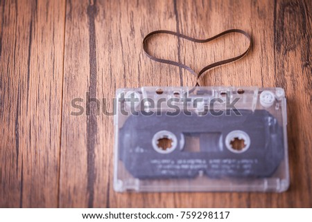 vintage love songs concept . audio cassette tape are Heart shape on the wooden table .  Customise retro vintage style colors tone . #759298117