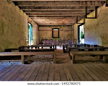 Vintage Low View Into an Empty Classroom With Benches in an Old Brick Building With Dirt Floor #1492780475