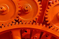 Vintage machinery cogwheels of a stone crusher in a decommissioned cement plant painted in striking orange color