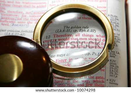 Vintage magnifying glass on a Holy Bible, highlighting the Golden Rule passage in Matthew Chapter 7 - King James Version (shallow focus).