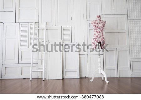 Vintage mannequin in cozy designer studio with ladder against the white wall and wooden laminate floor