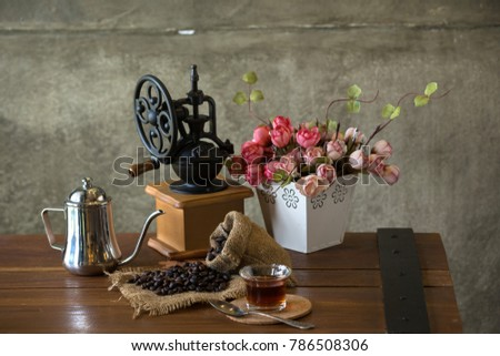 Vintage manual coffee grinder with coffee beans and cup.