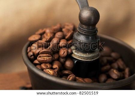 Vintage manual coffee grinder with coffee beans isolated - stock photo