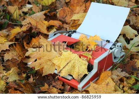 Vintage manual shabby typewriter, blank sheet of paper and fallen maple leaves in the fall - stock photo