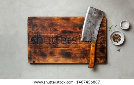 Vintage Meat cleaver on a empty old dark wooden cutting Board. Top view, space for text. Stock photo ©