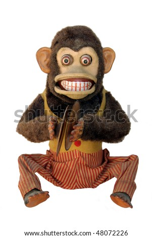 Vintage mechanical monkey with toy cymbals showing teeth, full body isolated on white
