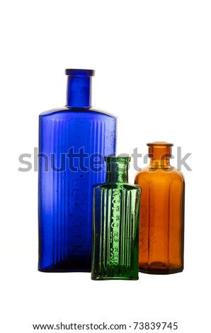 """Vintage medicine bottles; blue, green and brown poison bottles, isolated on white ground; moulded into the glass is the legend, """"Not to be taken"""""""