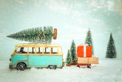 Vintage Merry Christmas postcard background - Miniature antique car carrying christmas tree on roof and presents (gift box) in snowy winter forest.