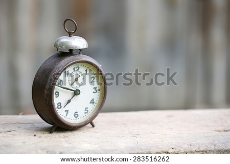 Vintage metal analog alarm clock with Arabic numbers and wind-up mechanism, sitting on a wooden bench with retro background. Time is now, time is money, old times concept.
