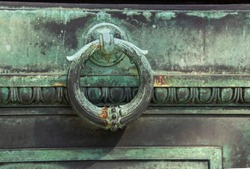 Vintage metal crypt door that is green from patina