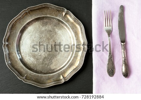 Vintage metal dish with silverware on slate background, with copy space for your menu or recipe. Table place setting. Top view.