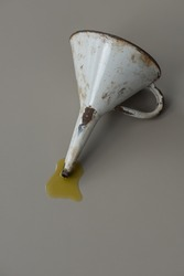 Vintage metal oil funnel, finished in white enamel with oil spillage on grey surface.