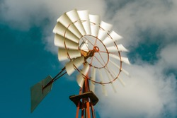 Vintage metal windmill rotating with blue sky and clouds. Energy and climate concept