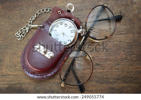 Vintage metallic glasses frame with pocket watch on the wooden table. Reading accessories.