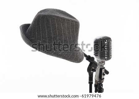 Vintage microphone on stand beside gray men's hat on second stand