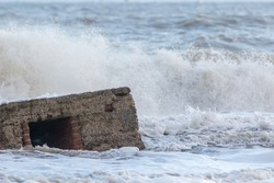 Vintage military defence building reclaimed by rising sea level. Close-up of 2nd world war sea defence building swallowed by tidal surge. Poignant remembrance and climate change image. Lest we forget