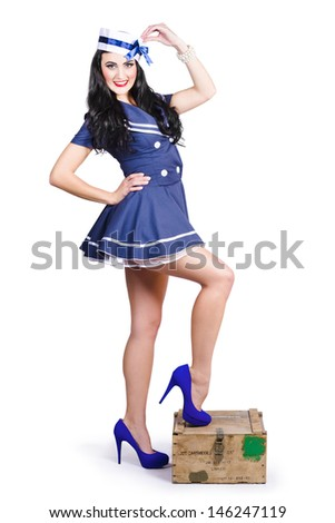 Vintage military photo of a beautiful navy woman in sailor outfit and hat standing on a resupply ammo box. Retro Pinups