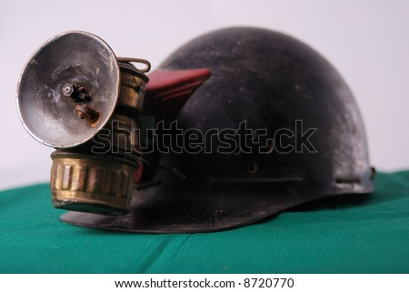 Vintage miner's helmet with carbide lamp - on green mat