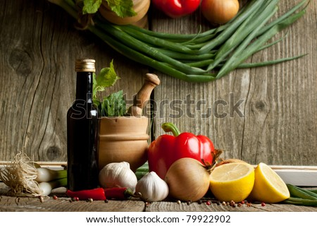 Vintage mortar and vegetables paprika, pepper and garlic on old wooden table with reflex in mirror