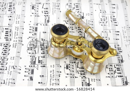 Vintage mother of pearl opera glasses made by Iris Paris about a hundred years ago sitting on an operatic score.