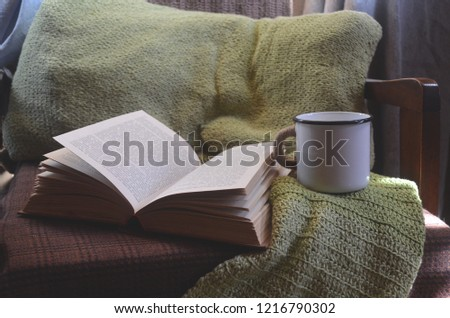 Vintage mug and old book on armchair with knitted pillow. Cozy atmosphere concept. Retro leisure. Vintage retro place relax hobby. Vintage literature and reading letter. Enjoy coziness at home. #1216790302