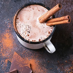 Vintage mug of hot chocolate with cinnamon sticks over dark background. Square image with selective focus