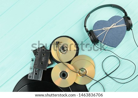Vintage musical objects on wooden background. Vinyl records, compact discs, analogue cassettes and headphones with heart-shaped gift box.