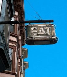 Vintage neon EAT sign mounted on side of building. Blue sky.