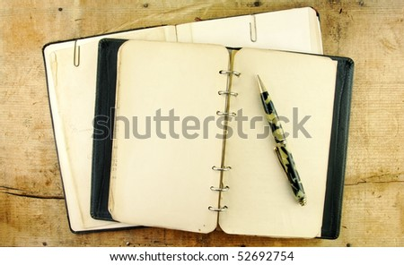 Vintage notebook and mechanical pencil on a rustic wooden table.
