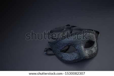 Vintage old black masquerade mask on the black background.Stylish and luxury background or decoration.Sexy and mysteriously carnaval style.New year party.Luxury lifestyle.Mysterious woman.