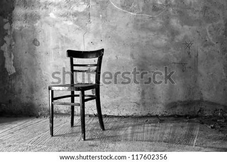 Vintage old black wooden chair in grungy interior. Loneliness, estrangement, alienation concept.