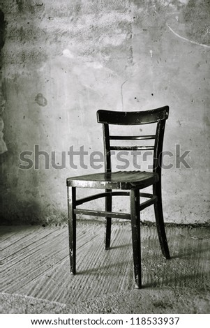 Vintage old black wooden chair in grungy interior. Loneliness, estrangement, alienation concept.