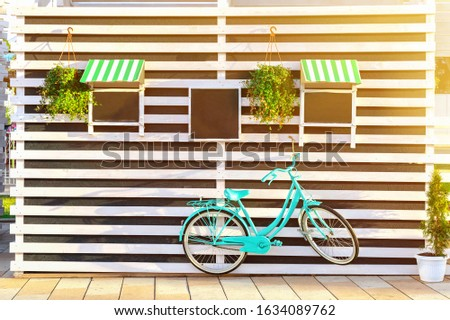 Vintage old blue bicycle near a store or bakery wall with wooden white boards in a rustic style with chalkboard, signboards with sunshades. Sunny morning horizontal background.