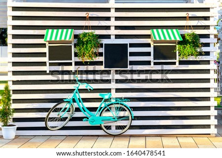Vintage old blue bicycle near a store or bakery wall with wooden white boards in a rustic style with black chalkboard, signboards with sunshades.