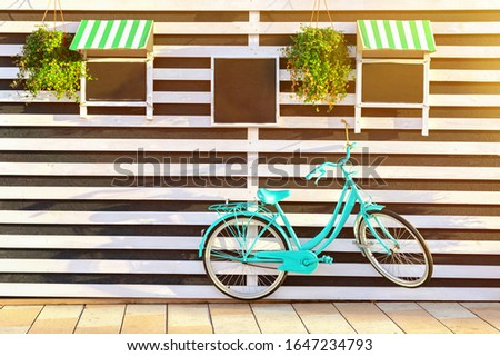 Vintage old blue bicycle near a store or bakery wall with wooden white boards in a rustic style with chalkboard, signboards with sunshades. Sunny morning background.