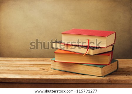 Vintage old books on wooden deck tabletop against grunge wall