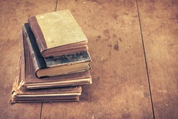 Vintage old books on wooden desk. Retro style filtered photo